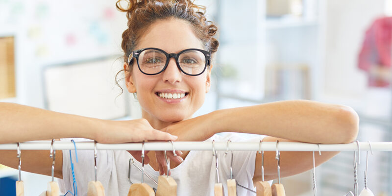 Smiling young designer looking at out of stand with clothes on hangers during work in office